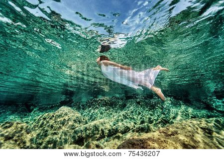 Swimming in transparent sea, emerges from clear sea, wearing fashionable white dress, luxury summer vacation, freedom and enjoyment concept
