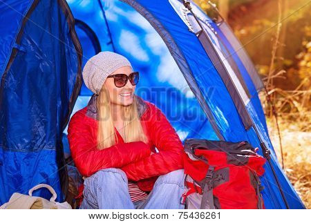 Happy smiling camper girl sitting in the tent, active lifestyle, autumn adventure, discovering world, travel and tourism concept