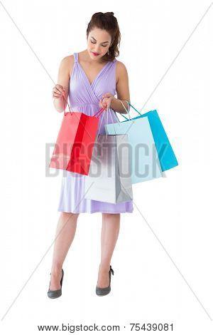 Stylish brunette in purpul dress opening shopping bag on white background