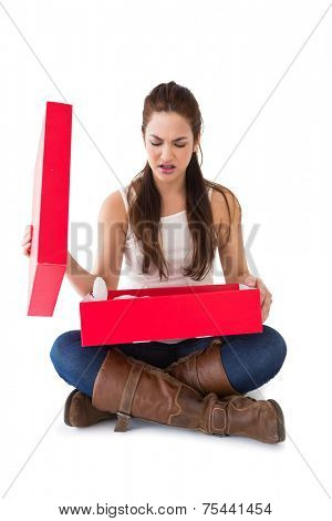 Unhappy brunette opening present on white background