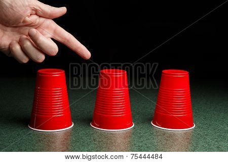 Three Red Cups And A Pointing Hand