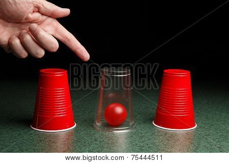 Red Ball Under Clear Cup With Hand