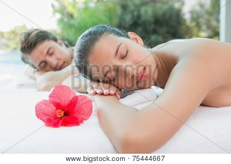 Relaxed young couple lying on massage table at spa center