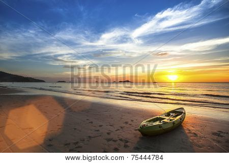 Tropical landscape. Canoe on the ocean beach during the amazing sunset.