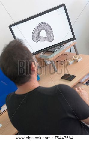 Worker in a dental lab pointing to computer screen