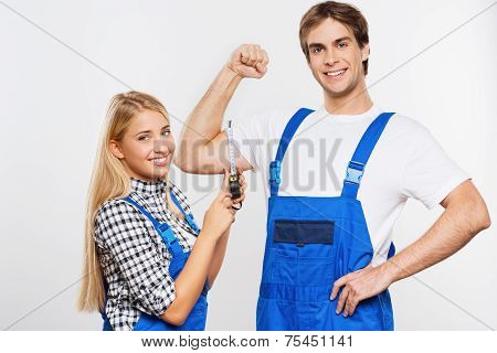 Young woman measuring repairman biceps