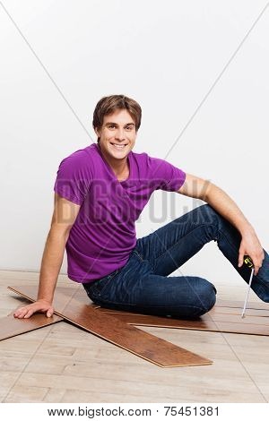 Young man measuring woodblock