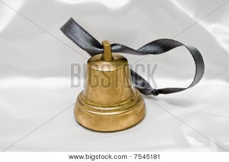 Small Handbell On White Silk Background