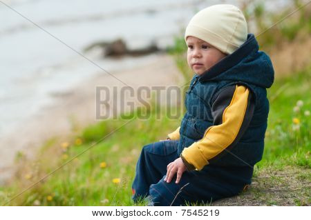 Young Boy Sitting On The Rocks Next To A Lake Lonely. He Is In Melancholy Mood