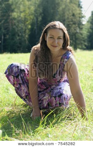 Young Woman In Light Dress Sitting On Green Grass In Field And Smile. Sunny Summer Time.