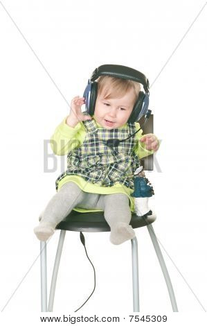 The Happy Small Child Sits On A Chair In Headset Ear-phones With A Microphone. Isolated On White Bac