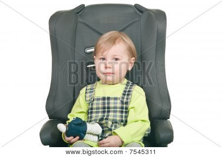 The Little Girl Sits In A Car Seat. It Is Isolated On A White Background
