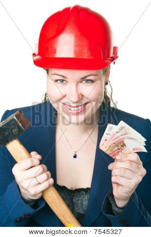 The Girl In A Building Helmet With A Hammer And Cash In Hands. It Is Isolated On A White Background