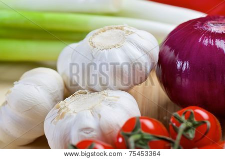 White garlic and purple onion on a wooden board
