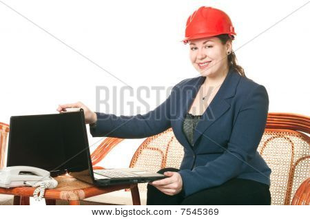 The Girl In A Red Helmet With The Laptop Sits At A Table. Isolated On White Background