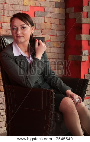 Young beautiful Business Woman sitting in Sessel Studio Interior