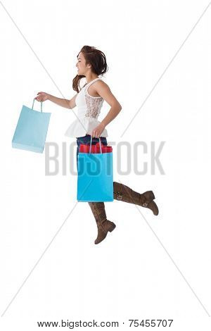 Happy brunette leaping with shopping bags on white background
