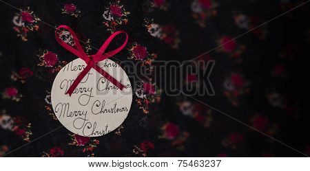 Round paper Christmas ornament with a red bow on floral fabric