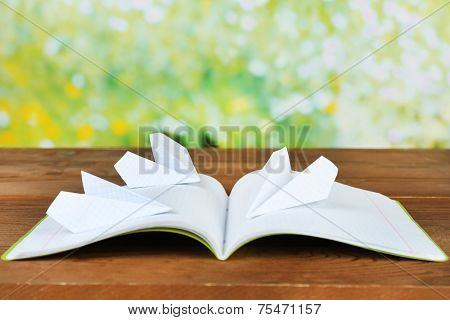 Origami airplanes on notebook, on wooden table, outdoors