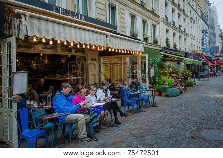 Family examines menu at a bistro in Paris