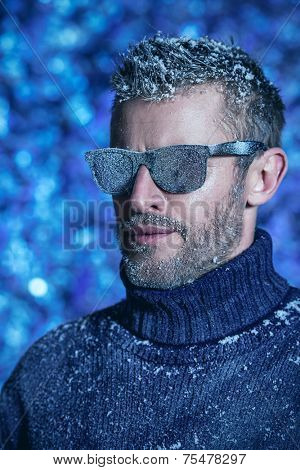 Portrait of a handsome brutal man dressed in winter clothes, covered with frost.