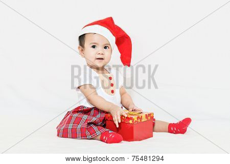 Photo Of Curious And Surprised Asian Baby In Santa Cap Looking At Giftbox In Hands
