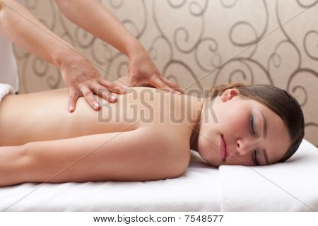 Woman Enjoying A Back Massage In A Spa Setting