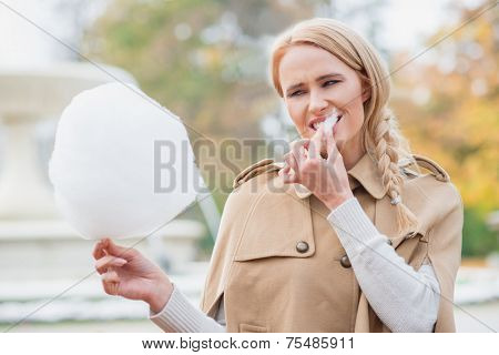 Pretty blond woman eating candy floss biting on a sticky morsel with a smile as she stands outdoors in an autumn park