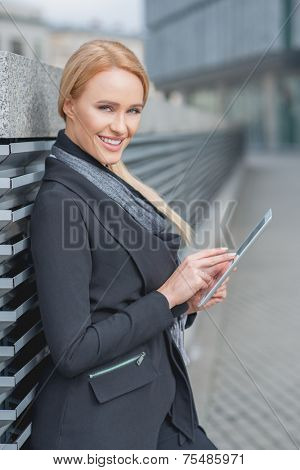 Stylish businesswoman using a tablet-pc as she leans against a metal louver along an urban walkway smiling at the camera