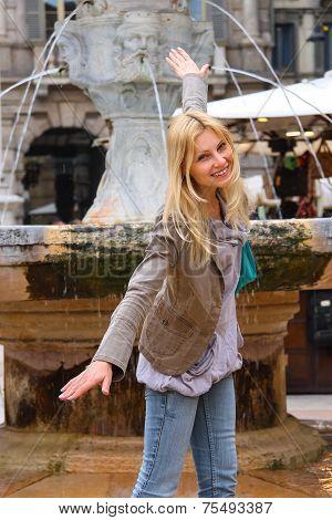 Attractive Girl Near A Fountain Of Madonna On Piazza Delle Erbe In Verona, Italy