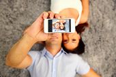 stock photo of love making  - Couple lying on the floor and making selfie photo on smartphone - JPG