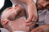 image of razor  - hairdresser  shaves  with blade of razor  face of   satisfied  client in  professional  hairdressing salon - JPG