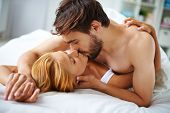 stock photo of intimate  - Passionate couple lying on bed and kissing - JPG