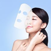 stock photo of sunburn  - Relax Young woman with cloth facial mask isolated on blue background concept for skin care and moisture asian beauty - JPG