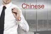 picture of pronunciation  - businessman in office writing chinese in the air language - JPG