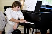 Serious Teenage Boy Looking Down At Piano Keys