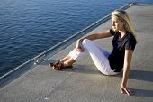 Pretty Teen Girl Sitting On Dock By Water Watching