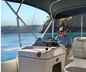 picture of pontoon boat  - Portrait view of mature man sitting at console of modern party pontoon boat against a background of turquoise sea cliff and distant ranges - JPG