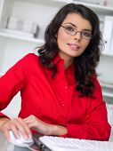 stock photo of woman red blouse  - Close up Young Office Woman Wearing Red Blouse and Eye Glasses Working at her Table Area with Computer - JPG