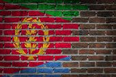 stock photo of eritrea  - Very old dark red brick wall texture with flag  - JPG