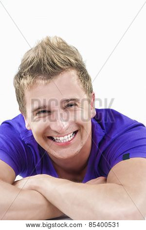 Closeup Portrait Of Happy Smiling Young Caucasian Handsome Tanned Man Laying Down With Hands Folded