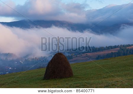 Autumn landscape. Beautiful clouds in the mountains. Haystack on the meadow
