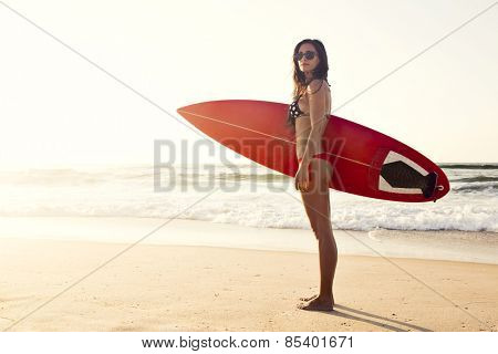A beuatiful and sexy surfer girl at the beach with her surfboard