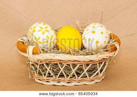 three easter colored eggs in basket with hay