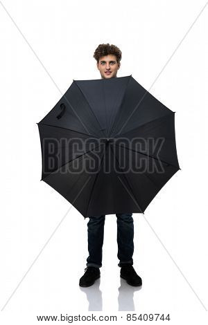 Young casual man holding an umbrella in front of him a