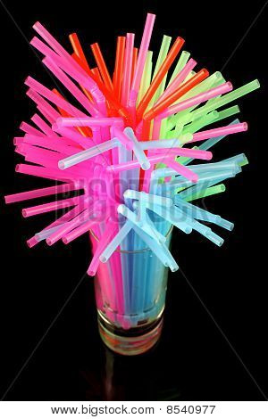 long drink glass with some water and many colored plastic straws