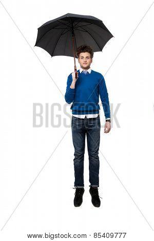 Handsome businessman standing under umbrella over white background