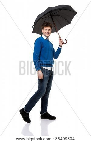 Full length portrait of a smiling man standing under umbrella