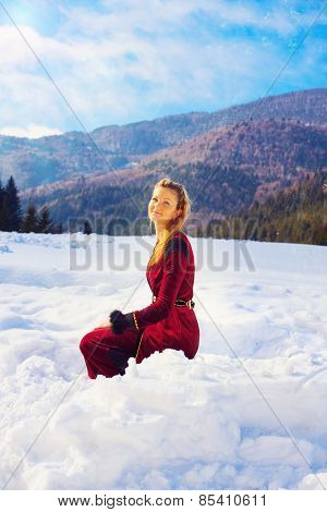 beautiful young blonde lady in medieval velvet clothing posing in the snowy mountain landscape