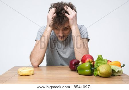 Pensive man sitting at the table with vegetables and donut